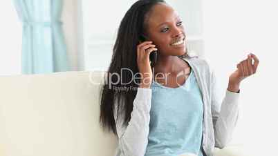 Woman sitting on a couch while talking on the phone
