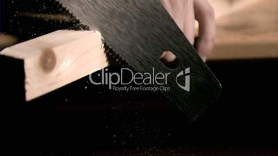 Man sawing in super slow motion a wooden board
