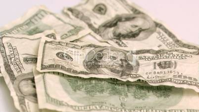 Wind blowing in super slow motion to show one hundred dollar banknote
