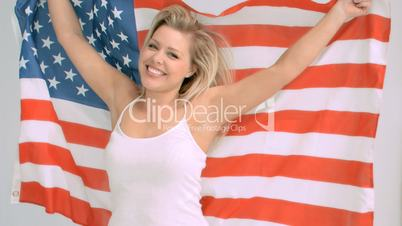 Smiling woman in slow motion holding the American flag