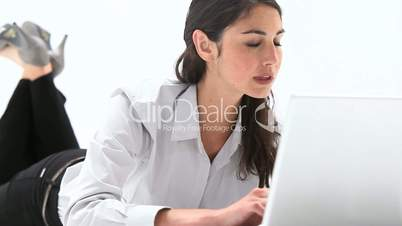 Woman lying on belly while using a laptop