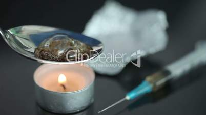 Boiling heroin in a spoon with a syringe being heated by a tea light