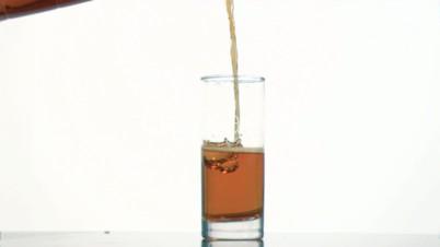 Brown fizzy drink flowing in super slow motion