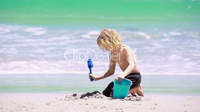 Blond kid playing on the beach