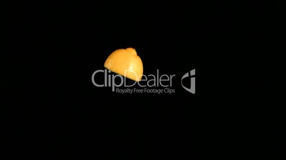 Yellow lemon slice rotating in super slow motion