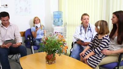 Female doctor talking to patient in a waiting room