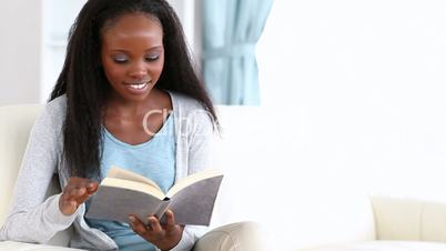 Woman reading a book while smiling