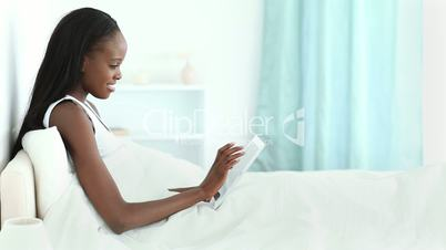 Woman lying on a bed while typing on a tablet