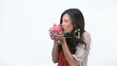 Happy woman kissing a piggy bank