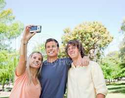 Close-up of three smiling students taking a pictures of themselv
