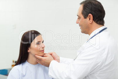 Doctor auscultating the neck of a patient