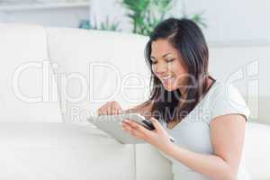 Smiling woman playing with a tactile tablet