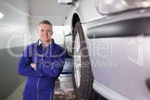 Front view of a mechanic smiling with arms crossed