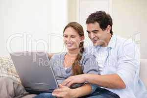 Couple sitting on a sofa while holding a laptop