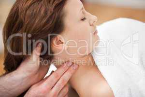 Therapist massaging the neck of woman while holding her head