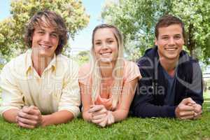 Portrait of three smiling students in a park