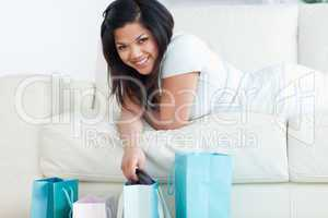 Woman laying on a sofa while holding up clothes from a shopping