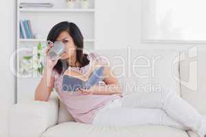 Woman drinking from a mug while lying on a sofa