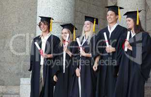 Smiling graduates posing while holding their diploma
