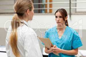 Nurse holding a file and talking to a doctor