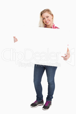 Blonde woman beaming while pointing at a placard