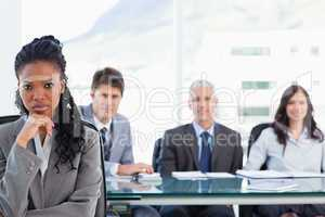 Businesswoman sitting with her hand on her chin in front of her