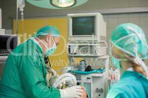 Surgeon holding a mask on the face of a patient