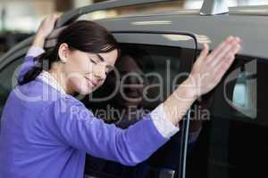 Woman hugging a grey car