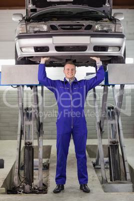Mechanic touching the below of a car