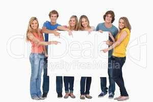Smiling group of people with a blank space as they point to it