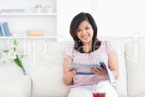 Woman sitting on a sofa while holding a magazine