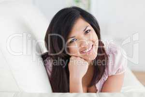 Smiling woman relaxing on a couch while holding her head with he