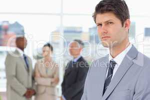 Serious businessman with a stern look standing in front of his c