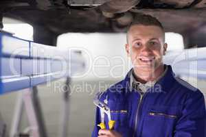 Smiling mechanic holding an adjustable pliers