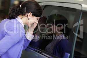 Woman looking inside a car