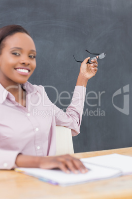 Teacher showing the blackboard with her glasses