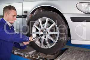 Mechanic unscrewing a bolt
