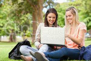 Laughing teenagers sitting while using a laptop