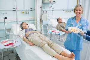 Nurse holding a plate of biscuits next to transfused patients
