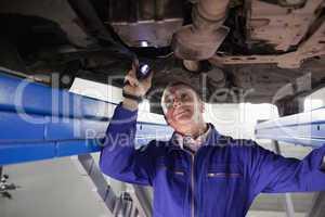 Smiling mechanic illuminating a car with a flashlight