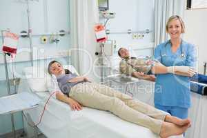 Two transfused patients next to a nurse