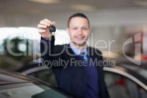 Dealer standing while holding car keys