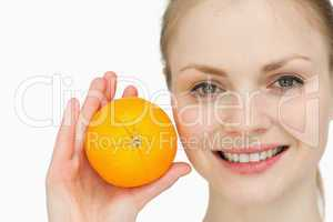fair-haired woman holding an orange