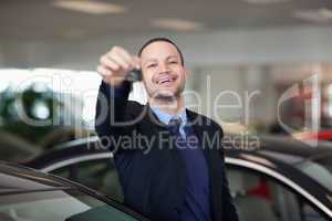 Salesman standing while holding car keys