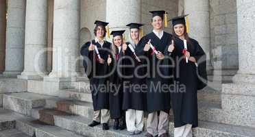 Five happy graduates posing the thumb-up