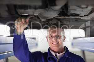 Smiling mechanic repairing a car with a spanner