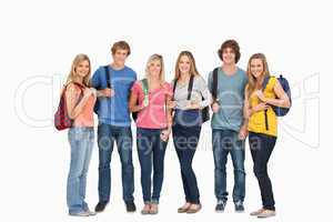 Smiling group with backpacks on as they smile
