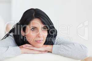 Woman crossing her arms under her head on a sofa