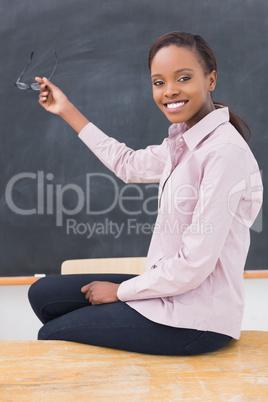 Teacher sitting on desk showing the blackboard