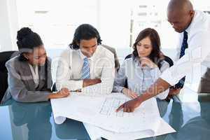 Young executive explaining an idea using flipchart sheets to co-